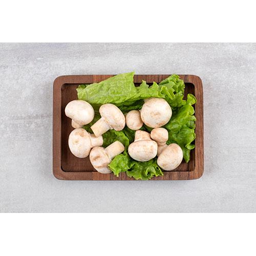 wooden plate full fresh champignon mushrooms placed stone table 1